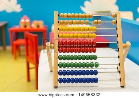 Educational math toy for children inside colorful room with red chairs and blue wall - Multicolor wooden abacus on the white desk - Concept of education learning and teaching - Main focus on red beads.