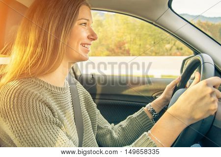 Young smiling woman drive a car on the road trip during sunny day. Pretty female travel in a new adventure along mountains streets. Concept of traveling and transportation with vintage filtered look.