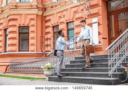 African American businessman and a Caucasian businessman shaking hands on the background buildings in the city