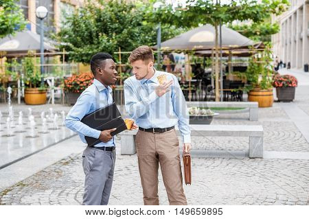African American businessman and a Caucasian businessman discussing and drinking coffee on city background, coffee break