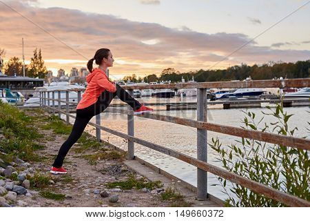 Adult person in sport wear stretch legs in evening training after running. Sport outdoor fitness concept for advertising with copy space for a text.
