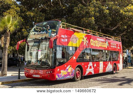 CADIZ, SPAIN - SEPTEMBER 27: Brightly decorated sightseeing double-decker open top bus in Cadiz takes visitors to all the major tourist attractions. September 27, 2016.