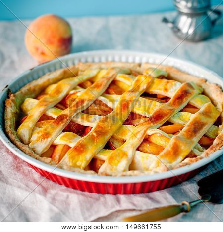 Peach pie, crostata in a baking dish on textile background Selective focus
