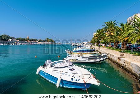ZADAR CROATIA - SEPTEMBER 14: Harbor in downtown Zadar with palm trees and walking path on a hot sunny day on September 14th 2016 in Zadar