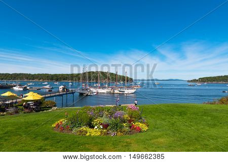 Bar Harborm Maine US -- Sept 22 2016--Boats large and small are anchored in Bar Harbor Maine. Some tourists are walking around; others are having lunch under yellow umbrellas in a restaurant by the water. Editorial Use Only.