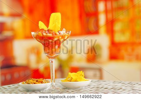 Traditional ecuadorian cold tomato based dish with chochos, onions and banana chips, elegant restaurant presentation.