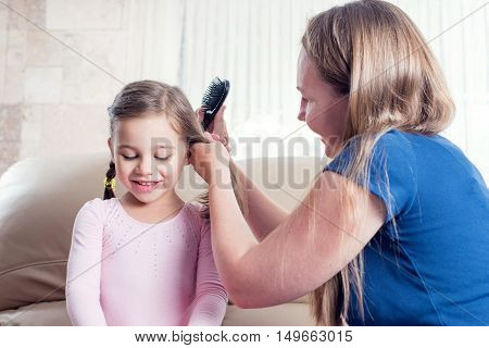 Mother is brushing her lovely daughters hair.