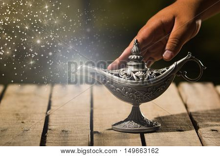 Beautiful antique metal lamp in true Aladin style, hand touching and animated star dust coming out, sitting on wooden surface.