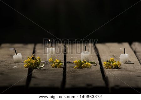 Four white wax candles sitting on wooden surface, no flames burning, with black background, beautiful light setting.