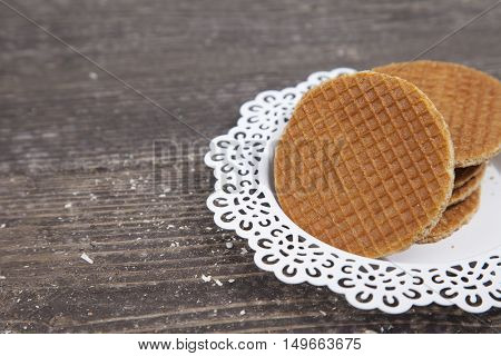 Dutch cookie stroopwafels on white plate on brown wooden background