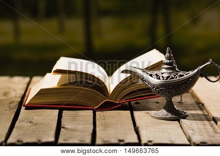 Thick book lying open on wooden surface, Aladin lamp sitting next to it, beautiful night light setting, magic concept shoot.