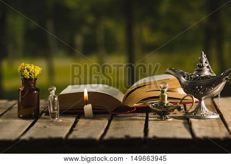 Thick book lying open on wooden surface, small brown bottle with flowers, Aladin style lamps and wax candle next to it, magic concept shoot.