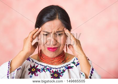 Headshot beautiful hispanic mother wearing traditional andean clothing, simulating headache using hands touching forehead, painful facial expression, pink studio background.