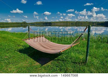 Relaxing Hammock on a Russian lake shore under summer sunshine