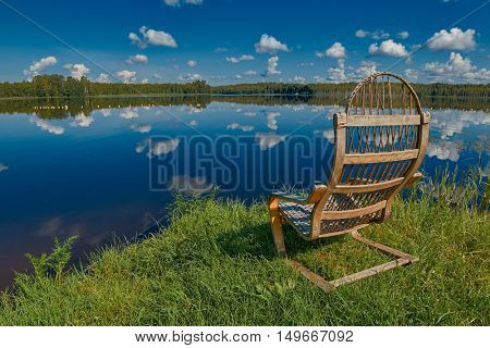 Idyllic Relaxing Russian Lake Beach Landscape with Wooden Chair