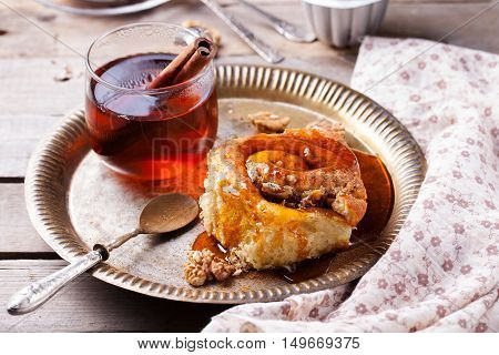 Cinnamon bun rolls with syrup and tea on a wooden background