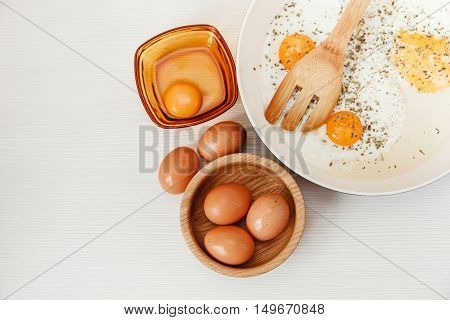 Fried eggs in the frying pan.breakfast ingredients.kitchen accessories.Fresh Brown Eggs in the Wooden Plate.White Background.Top View