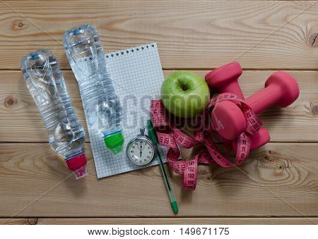 Fitness concept with dumbbells. bottle of water measure tape apples notebook and stopwatch.