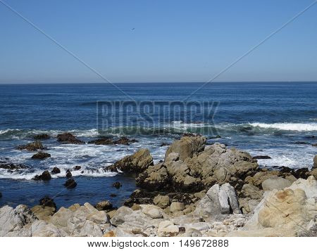 This is an image of rocks and the incoming tide at Asilomar Beach in Pacific Grove, California.
