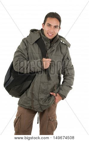 latin  guy wearing coat and backpack posing with hand on pocket isolated on white