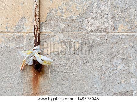 Old rusty rain pipe on grey vintage wall.