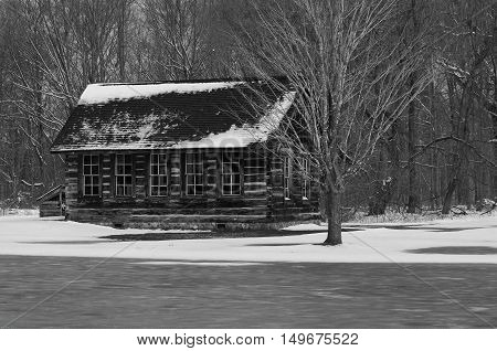 snowy cabin set in the woods in black and white.