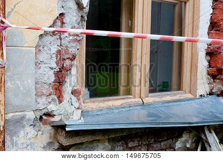 Window on old broken wall with visible bricks behind the red and white warning tape.