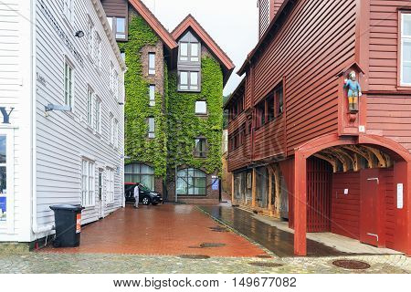 BERGEN, NORWAY - JULY 2, 2016: This is part of the port quarter Bryggen where next to the old historic houses appear stylized modern home entwined with climbing plants.