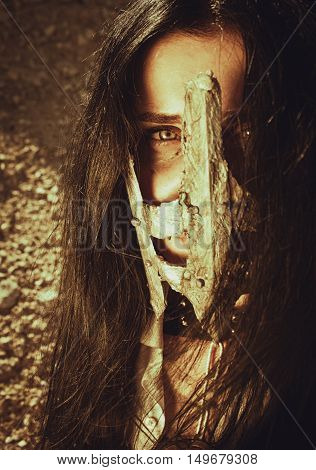 Pretty girl in iron mask over wasteland