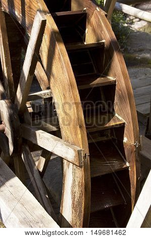 Old fashioned weathered brown wooden water wheel at Capilano BC on a bright sunny day.