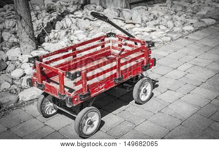 horizontal black and white image of an old wooden child's wagon spot colour in red sitting on a cement pad.