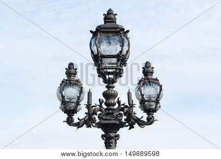 Parisian lamppost closeup against clear sky in Paris, France