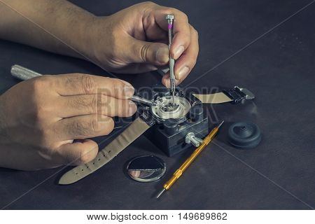 watchmaker try to repair watch on tools and table with vintage filter - can use to display or montage on produxts