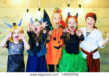 Happy group of witch children pirate and demons during Halloween party playing around the table with pumpkins