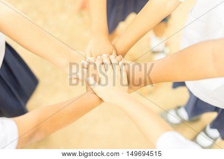 Children making pile of hands teamwork concept soft focus