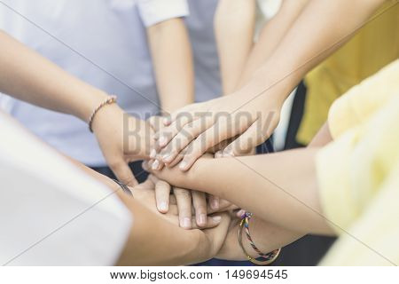 Children making pile of hands teamwork concept soft focus vintage tone