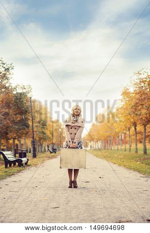 Beautiful girl with a suitcase in a park. Autumn background. Traveling concept.