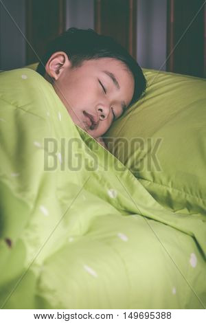 Healthy children concept. Closeup of asian child sleeping peacefully. Cute boy sleep tight on bed in the bedroom at night. Vintage tone effect.
