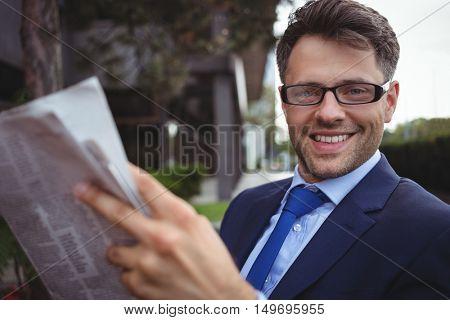 Portrait of handsome businessman reading newspaper outside office
