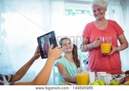 Boy photographing his grandmother and sister at home