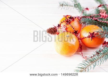 Ripe mandarins with fir-tree branch on a white background