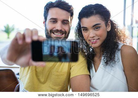 Smiling couple taking a selfie in coffee shop