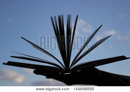 silhouette of open book in hand on blue sky background