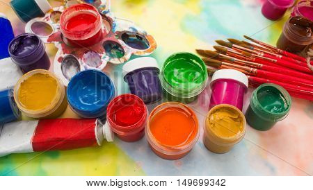 Paints, brushes and palette on the colorful background. The workplace of the artist. Banner for school
