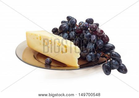Piece of a Swiss-type cheese and cluster of a blue table grapes on a dark glass dish on a light background