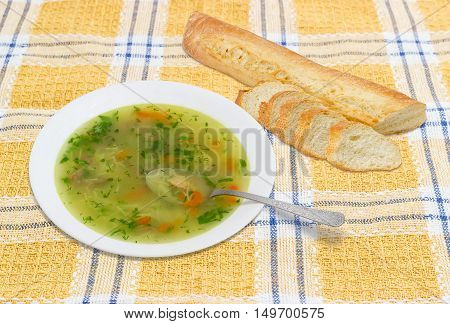 Homemade chicken soup in white dish with a spoon and partly sliced baguette on checkered tablecloth