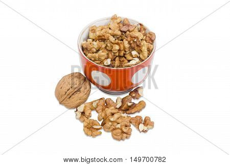 One whole walnut in their shell and shelled kernels in a cup and separately on a light background