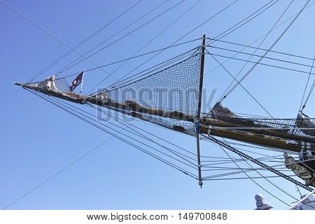 View of a bowsprit of a large wooden sailboat against blue sky