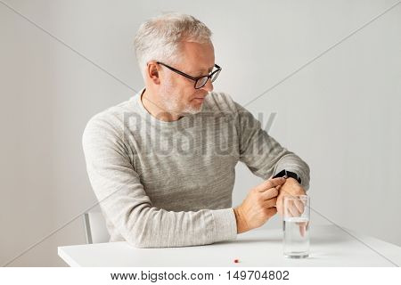 medicine, healthcare and people concept - senior man with glass of water water and pill looking at wristwatch or smartwatch with health application at home