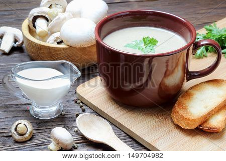 Mushroom soup puree of champignon in a brown cup on a wooden table